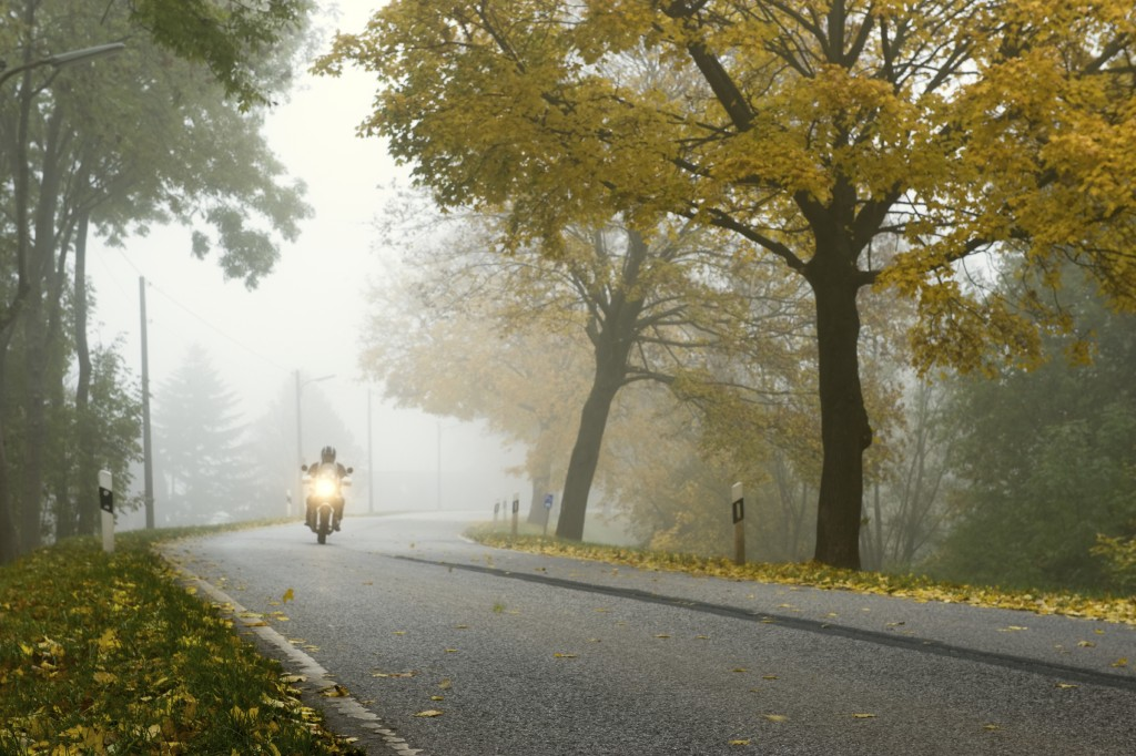 Driving bike in autumn in a foggy morning