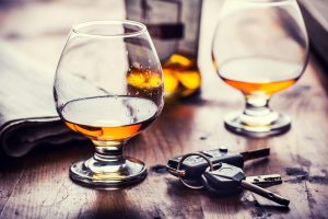 Picture of Two Glasses of Cognac with Car Keys Sitting on the Table Between Them